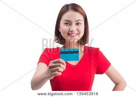 Beautiful friendly smiling asian girl showing credit card in hand over blue background