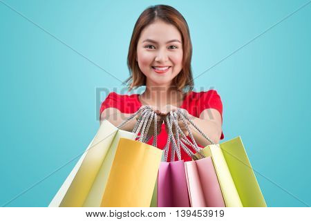Beautiful young asian woman with colored shopping bags over blue background. Focus on bags.