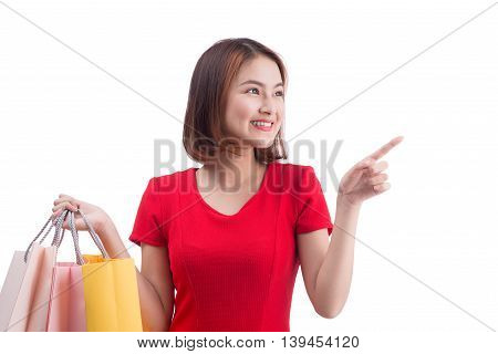 Shopping woman smiling joyful and happy holding shopping bags pointing. Asian female shopper isolated on white.