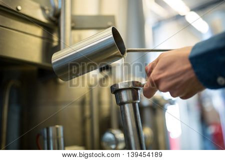 Close-up of brewer checking beer at brewery