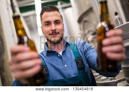 Portrait of handsome brewer holding two beer bottle at brewery