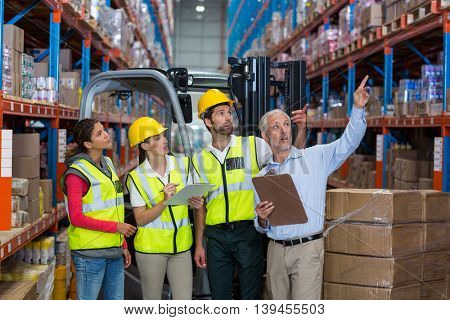Manager and workers are looking shelves and pointing in a warehouse
