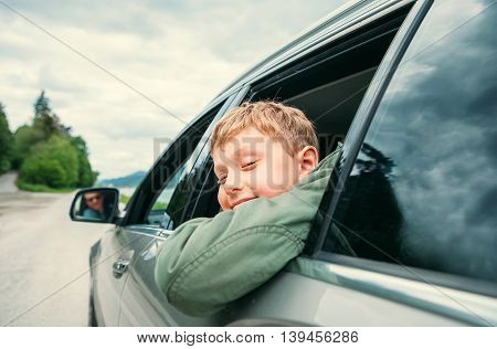 Boy looks out from the car window