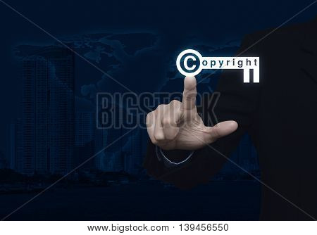 Businessman pressing copyright key icon over map and city tower background Copyright and patents concept Elements of this image furnished by NASA