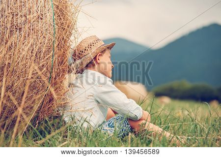 Dreaming boy sitting nea the rolled haystack