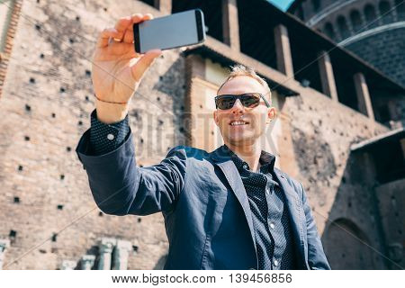 Man take a self picture with his smartphone near the old castle