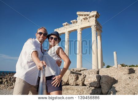 Smiling young couple take a selfie photo on antique ruins. Temple of Apollo Side Turkey