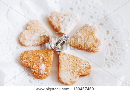 Golden wedding rings with diamonds lie with sweet heart shaped cookies. Symbol of love and marriage.