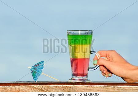 Female hand holding a glass with colorful cocktail on the background of the sea umbrella for cocktails