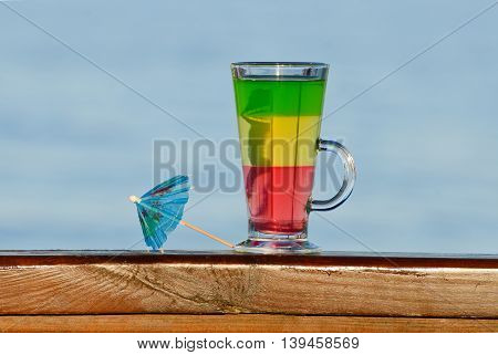 A glass with multi-colored cocktails and cocktail umbrella against the sea