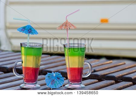 Two glasses with colorful cocktails and straws on a wooden lounger on the background Autocamper