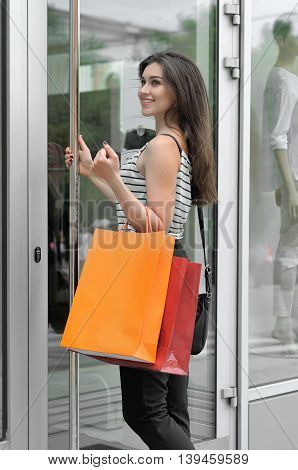 Smiling Girl Walks Into A Glass Door Shop.