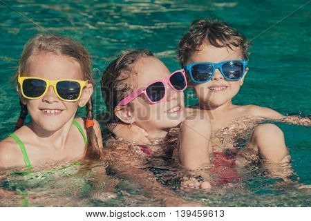 Three happy children playing on the swimming pool at the day time. Kids having fun outdoors. Concept of friendly family.