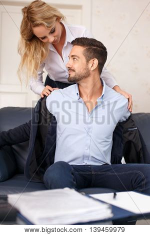 Young secretary helps put off businessman suit in office seduction