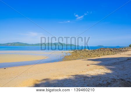 Surfer on Pretty beach and ocean with sky and clouds in distance