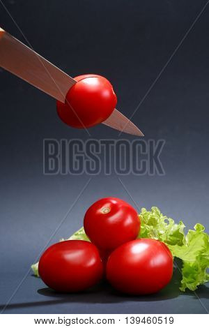Cooking concept. Few freshness red tomatoes and knife on dark background