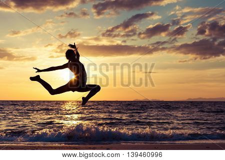 Happy teen girl jumping on the beach at the sunset time. One teenager having fun on the nature. Concept of happiness.
