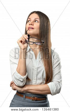 Young thoughtful businesswoman looking upwards with glasses in her arm isolated on the whire background. Business staff. Office clothes. Ideas and concepts. Contemplations and reflections.
