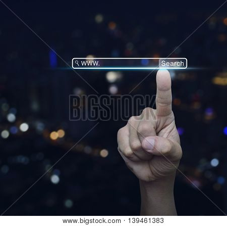 Hand pressing search www button over blur light city tower background Searching system and internet concept