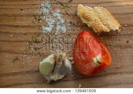 A piece of bread tomatoes and garlic on a wooden background.