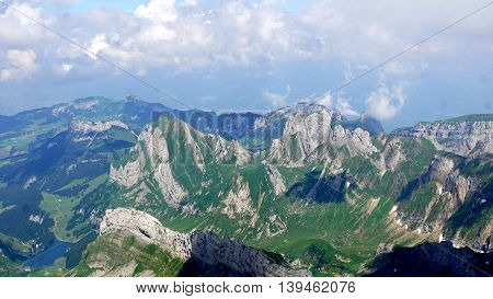 Mountain world in Switzerland, view from Säntis on the Alpstein-Massif with the Lake Seealp in the Appenzellerland, steep rocks and snow fields,