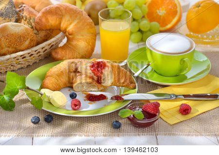 Breakfast table with a cup of cappuccino and fresh croissants with butter and jam