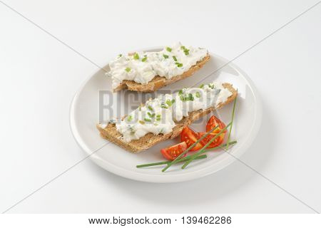 halved whole wheat bread roll with cheese spread