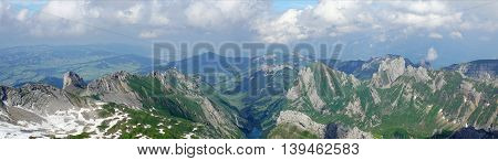 Mountain world in Switzerland, view from Säntis on the Alpstein-Massif with the Lake Seealp in the Appenzellerland, steep rocks and snow fields, panoramic,
