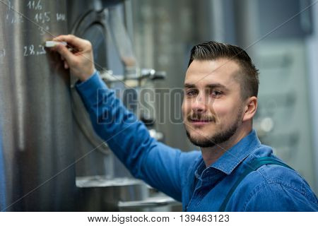 Portrait of happy maintained worker writing on tank at brewery