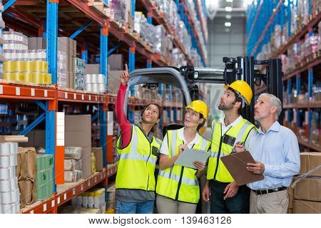 Worker showing shelves to her colleagues and manager in a warehouse