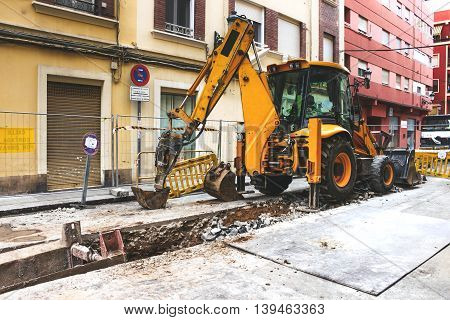 Yellow tractor works on the old street water-pipe