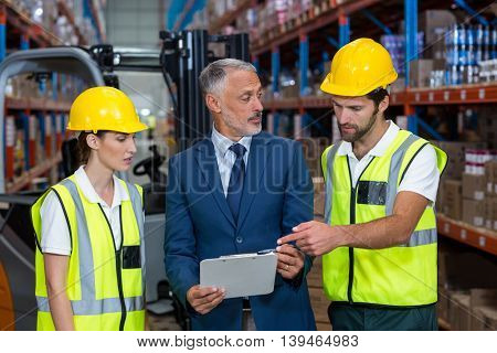 Manager and workers are talking and looking a tablet in a warehouse