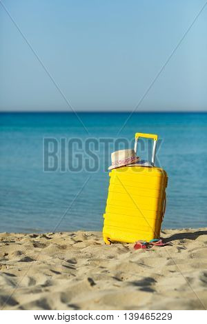 Travel holiday vacation suitcase with map straw hat and beach slippers on the beautiful sand beach. Advertisement travel suitcase