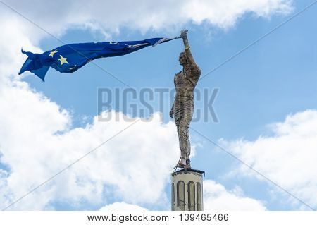 Antike stone statue holds a European flag in his hand.