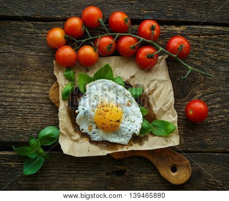 Scrambled eggs on toasted bread with basil spices and cherry tomatoes on a wooden background