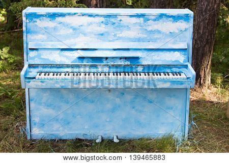 blue piano standing on the ground in the forest