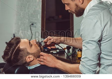 Hipster client visiting barber shop. The hands of young barber making the cut of beard