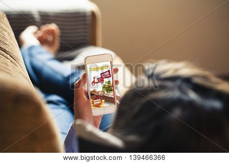 Woman ordering food by internet with a smartphone while lying on a sofa at home.