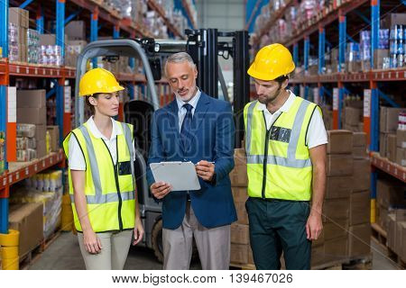 Manager showing tablet to workers in a warehouse