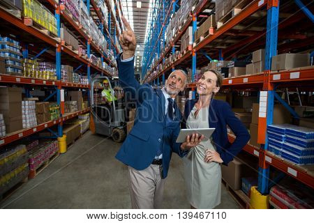 Managers are looking up and pointing shelves in a warehouse