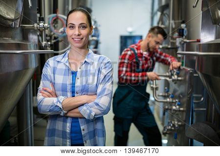 Portrait of female maintenance worker standing with arms crossed at brewery