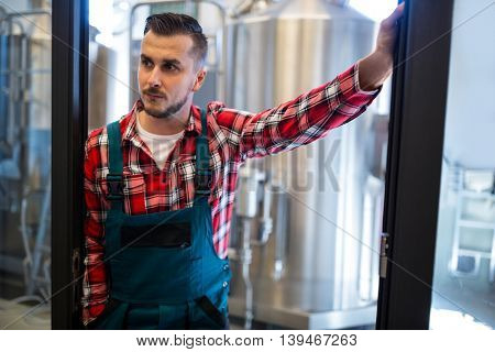 Thoughtful brewer standing at brewery