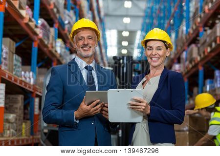 Managers are holding a tablet and looking the camera in a warehouse
