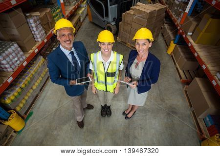 High angle view of managers and worker wearing hard hat and looking the camera in a warehouse