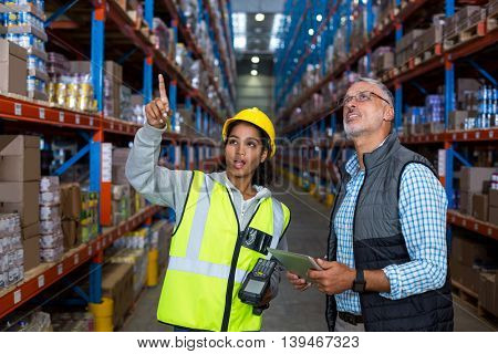 Worker showing shelves to her manager in a warehouse
