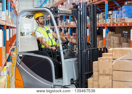 Worker is driving a pallet truck in a warehouse