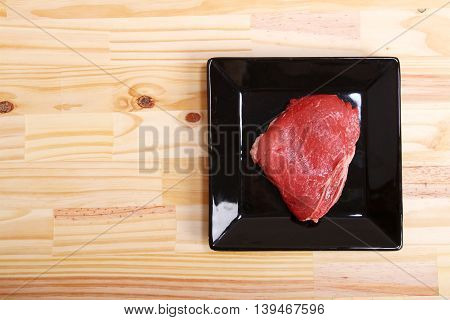 Some raw meat on a Plate. Digital photo.