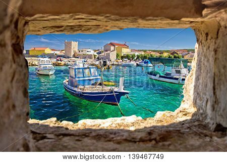 Razanac turquoise waterfront through stone window Dalmatia Croatia