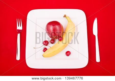 A white plate with fruit on red background.