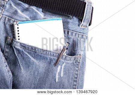 A notebook in some jeans trousers. Digital photo.